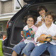 Siblings sitting on tailgate of car playing toy instruments - Stock Photo