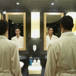 Stock Photo: Two men in robes in front of bathroom mirrors