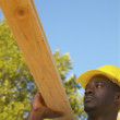 Male construction worker carrying two by fours — Stock Photo
