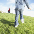 Rear view of two children running through grass — Stock Photo