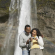 Photo: Couple looking at digital camera in front of waterfall