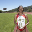 Winning female track athlete holding trophy - Stock Photo