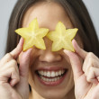 Foto de Stock  : Asian woman holding star fruits over eyes