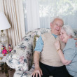 Senior couple hugging on sofa — 图库照片