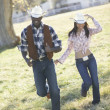 Couple in cowboy outfits walking together - Stock Photo