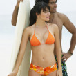 South American couple holding surfboard - Foto Stock