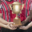 Soccer players holding trophy — Stock Photo