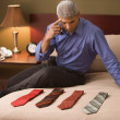 Businessman picking out a tie - Stock Photo