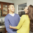 Young Hispanic couple hugging in the kitchen — Stock Photo
