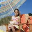 Royalty-Free Stock Photo: Portrait of girl sitting in chair with umbrella at beach