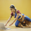 Exotic woman reaching for laptop computer — Stock Photo