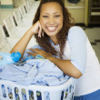 Portrait of womwith basket of clothes in laundromat — Stock Photo #13227157