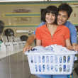 Portrait of couple with laundry hugging at laundromat — Stock Photo #13227169