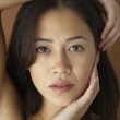Asian woman with hand on face — Stock Photo