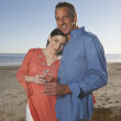 Portrait of couple at beach hugging with wine glasses - Stock Photo