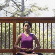 Woman meditating on deck — Stockfoto