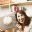 Woman holding up gift - Foto Stock