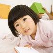 Asian girl holding book in bed — Stock Photo