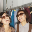 Stock Photo: Young women trying on sunglasses