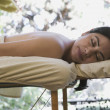 Hispanic woman lying on a massage table - Stock Photo