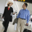 Businesspeople with luggage at airport — Stock Photo