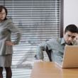 Businessman working under colleague's scrutiny — ストック写真