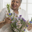 Senior woman arranging flowers — Stock Photo