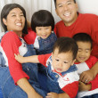 Stock Photo: Portrait of Asian family on bed