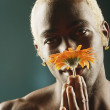Young man smelling orange flower — Stock Photo #13227380