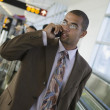 Stock Photo: Businessman talking on cell phone at airport