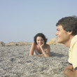 Young couple laying in sun on beach — Stock Photo