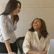 Businesswomen laughing at desk — Stock Photo