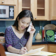 Woman writing while talking on phone — Stockfoto