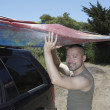 Man lifting kayak onto SUV roof — Stock Photo