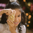Stock Photo: Hispanic girl holding Christmas gift in front of face