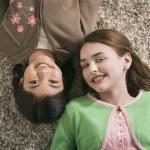Two girls lying on floor smiling — Stock Photo