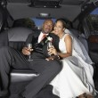 图库照片: Newlyweds drinking champagne in their limo