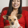 Stock Photo: Hispanic womsmiling with small dog on lap