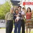 Multi-generational Asian family holding up Sold sign in front of house — Стоковое фото