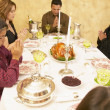 Hispanic family saying grace at dinner table — Stock Photo