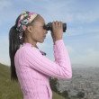 Royalty-Free Stock Photo: African woman using binoculars over city