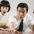 Asian man and woman putting together puzzle - Stock Photo