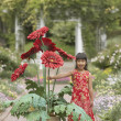 Asian girl in garden with giant potted plant — Stok fotoğraf