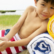 Boy laying on towels at beach — Stock Photo