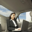 Stock Photo: Businesswoman working in the backseat of a car