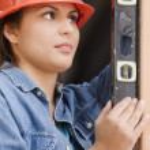 Hispanic female construction worker using a level — Stock Photo