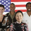 Multi-ethnic standing in front of American flag - Stock Photo
