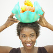 Portrait of woman holding bowl of fruit on head — Stock Photo #13227810