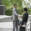 Stock Photo: Two businessmen shaking hands on stairs outdoors