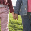 Stock Photo: Midsection of two young girls holding hands
